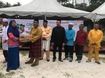 Yahanis (enam kanan) menyampaikan sumbangan kepada masyarakat orang asli di Kampung Sungai Perah, Parit, pada majlis tersebut baru-baru ini.