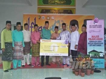 Dr Sahruddin (lima dari kiri) menyerahkan replika cek peruntukan membina surau SK LKTP Bukit Ramun kepada Md Noh ketika hadir Majlis Berbuka Puasa dan Solat Tarawih di Masjid Felda Bukit Ramun kelmarin.