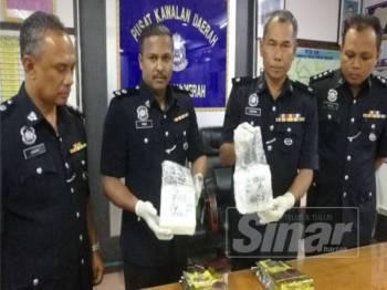 Suzaimi (dua, kanan) menunjukkan dadah jenis syabu bernilai RM100,000 yang berjaya dirampas pihaknya dalam serbuan Ahad lalu.