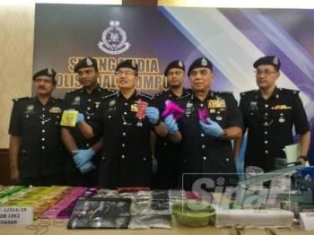 Mazlan (tiga, kiri) menunjukkan antara paket dadah yang dirampas dalam serbuan di sebuah kondominium di Cheras, Kuala Lumpur, Khamis lalu.