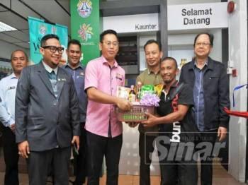 Mohd Hafiz (tengah) menyerahkan sumbangan Sudut Wakaf kepada Abdul Rahim (dua dari kiri) di MDYP.