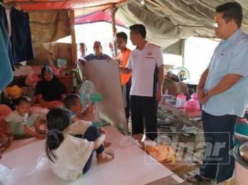 Dr Md Farid ( kanan) dan Tung Siong ( tengah) melihat keadaan Norhaslinda dan anak- anak  tinggal di bangsal berbumbungkan kanvas, di Kampung Maju Jaya, Pekan Nanas semalam.