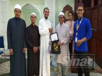 Asmuni (dua, kanan) menerima cenderahati daripada Penasihat Utama YDKMM, Dr Mohd Hizul Azri Md Noor selepas menyempurnakan pelancaran program berkenaan di Masjid Sultan Idris Shah ll (Masjid Negeri Perak) di sini.