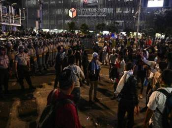 Polis Indonesia berdepan penunjuk perasaan ketika demonstrasi di luar pejabat Badan Pengawas Pemilu (Bawaslu) di Jakarta malam semalam. - FOTO AFP