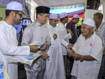 Datuk Seri Mohamed Azmin Ali (dua, kiri) menyampaikan sumbangan kepada golongan asnaf pada Majlis Iftar Perdana dan Penyerahan Sumbangan Hari Raya Aidilfitri di Surau Jabal Nur Sri Gombak Hari ini. Foto: Bernama