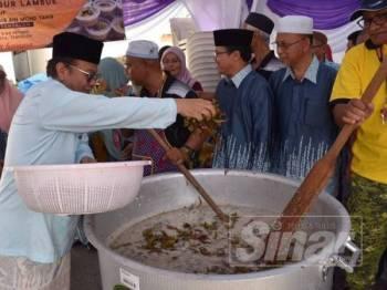 Mohd Anuar ketika membantu menyediakan bubur lambuk di pekarangan masjid tersebut hari ini.