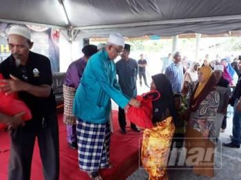Mahfuz (dua, kiri) menyampaikan sumbangan kepada asnaf yang terpilih di Masjid Al Kauthar, Titi Besi, Alor Setar petang tadi.