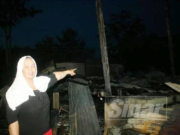 Noriah menunjukkan rumah jiran yang terletak di hadapan rumahnya musnah dalam kebakaran.
