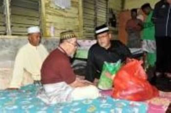 Aminolhuda (kanan) sewaktu menziarahi asnaf di DUN Parit Yaani di Masjid Felcra Sri Wangi, di sini, malam tadi.