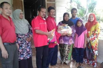 Fauzi Long (empat dari kiri) menyampaikan sumbangan kepada Hasnaf di Kampung Pandu di sini.