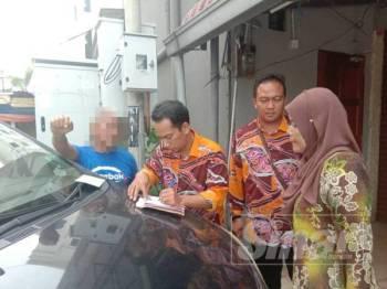 Anggota penguat kuasa mengeluarkan notis tidak menghormati Ramadan kepada seorang warga emas (kiri).