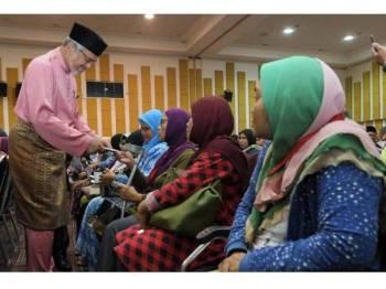 Menteri Wilayah Persekutuan Khalid Abdul Samad (kiri) menyampaikan sumbangan kepada sebahagian penerima pada Majlis Sumbangan Aidilfitri Komuniti Kuala Lumpur di Dewan Perdana Mestika Institut Latihan DBKL hari ini.