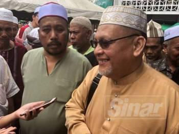 Mohd Amar (kanan) menasihati orang ramai supaya tidak membaling kon pada kenderaan yang terperangkap dalam kesesakan orang ramai yang membeli belah.