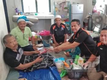 Muhammad Yusri (dua, kanan) diiringi ahli jawatankuasa PKABAS menyampaikan sumbangan kepada Abe Jali.