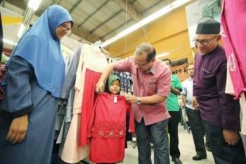 Ahmad Amzad (dua dari kanan) melayan salah seorang penerima sumbangan memilih baju raya di Pasaraya Mydin Mall, di sini.