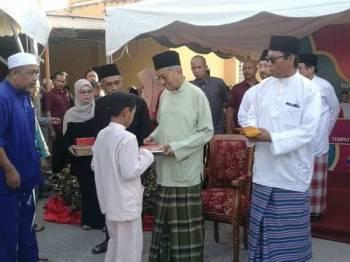 Dr Mahathir (tengah) menyerahkan sumbangan kepada kanak-kanak pada Majlis Berbuka Puasa dan Kebajikan bersama Perdana Menteri di Masjid Nurus Salam, Ewa, di sini tadi.