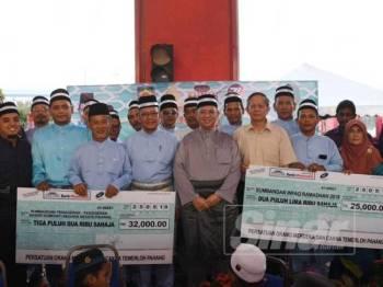 Saifuddin (tengah) bersama penerima sumbangan dalam program tersebut hari ini.