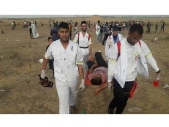 Seorang lelaki Palestin yang cedera diusung ke kawasan selamat oleh anggota paramedik.