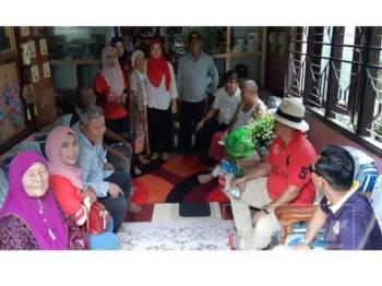 Mohd Rafiq (tengah) ketika menyantuni rumah seorang penduduk di Kampung Lanjut Manis, Krubong, di sini hari ini.