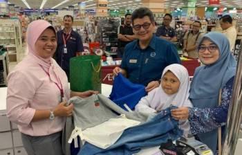 Mohd Azhar (tiga, kanan) bergambar bersama salah seorang penerima dalam program berkenaan.