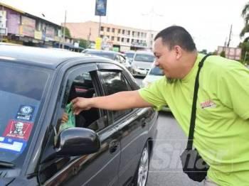 Ahmad Nazmi mengagihkan ABC kepada pengguna jalan raya di lampu isyarat Pulau Kambing, Kuala Terengganu, semalam.