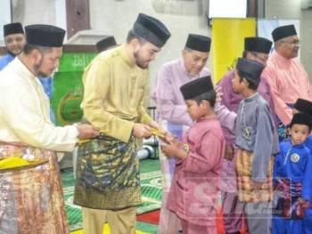 Tengku Amir Shah menyampaikan sumbangan kepada salah seorang anak yatim di Masjid At-Taqwa, Kampung Selayang Baru, di sini hari ini.