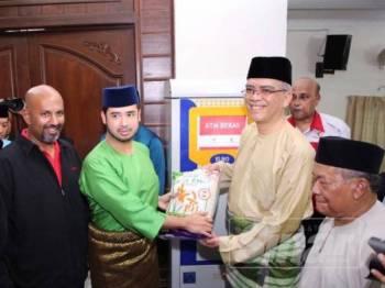Tunku Idris (dua,kiri) menerima satu bungkusan beras dari Khairil untuk diisi ke dalam mesin ATM berkenaan sebagai gimik pelancaran majlis di Masjid India hari ini.