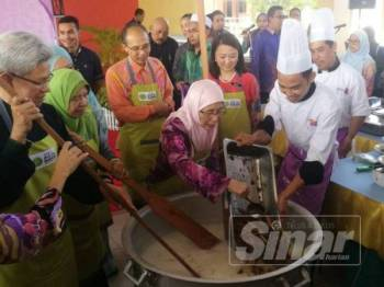 Dr Wan Azizah memasukan ramuan yang disediakan bagi menyiapkan bubur lambuk resepi Istana Pahang.