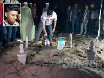 Muhammad Adib menyiram air di pusara kedua-dua ibu bapanya yang selamat disemadikan dalam satu liang lahad di Tanah Perkuburan Islam Kampung Dura Tengah, Dungun.