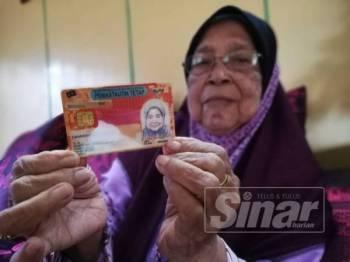 Zaharah menunjukkan kad pengenalan merah yang digunakan selama 40 tahun.