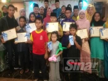 Fadhilah (tengah) bersama sebahagian anak angkat di bawah Perkeso yang diraikan dan menerima sijil anak angkat dalam satu majlis di satu majlis di Hotel Sentral Riverview, di sini, malam tadi.