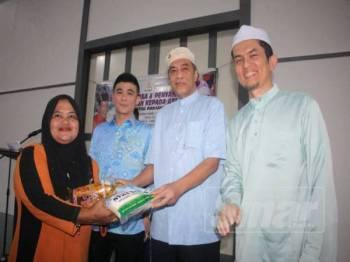 Husam (dua, kanan) menyerahkan sumbangan pada Majlis Berbuka Puasa dan Sumbangan kepada Asnaf Rantau Panjang di Kilang LLY Loyalty Logistics Sdn Bhd, Rantau Panjang.