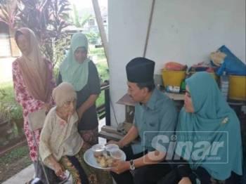 Mohd Zawawi ketika menyantuni warga emas sempena Program Yuk Munjung di DUN Sungai Kandis, kelmarin.