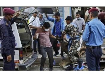 Mayat salah seorang mangsa yang maut dibawa keluar dari lokasi insiden letupan di Kathmandu. - Foto AP