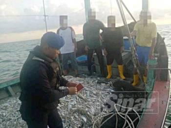 Anggota PPM Wilayah 2 Muar memeriksa dokumen juragan dan awak-awak yang berada di atas bot.