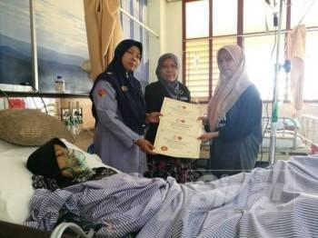 Farihah (kiri) menyampaikan bayaran faedah pengurusan mayat sebanyak RM2,000 dan pencen penakat yang diwakili Nurul Umiraf (kanan) anak sulung pasangan yang maut dalam nahas di Setiu.