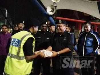 Aidi (tengah) menyerahkan juadah sahur kepada salah seorang anggota polis yang bertugas.