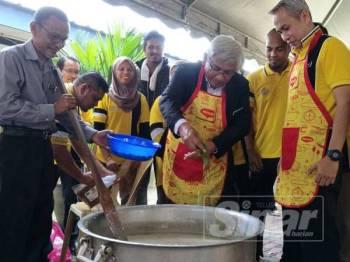 Abdul Aziz memasukkan bahan tambahan kepada bubur lambuk yang dimasak pada Program Gotong Royong Bubur Lambuk Peringkat Jabatan Pendidikan Negeri (JPN) Perak di Atrium Gemilang JPN.