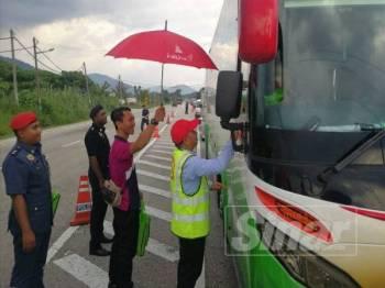 Musa mengagihkan barangan cenderahati kepada pengguna jalan raya pada majlis tersebut di Stesen Penguatkuasa Jabatan Pengangkutan Jalan (JPJ) Kalumpang kelmarin.