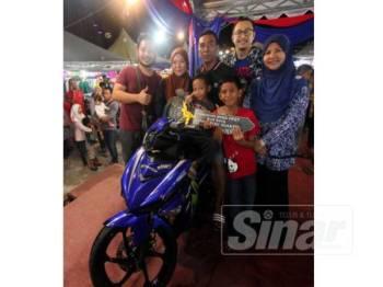 Rohana ( kanan) dan Tengku Azni Zazillah (tengah) bersama motosikal dimenangi pada cabutan bertuah tersebut.