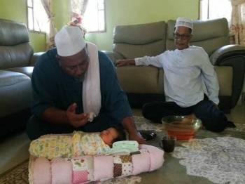 Allahyarham Ustaz Din ketika melakukan tahnik seorang bayi sambil diperhatikan Sanusi di sebuah rumah penduduk baru-baru ini.