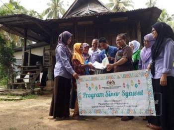 Ismail (empat kanan) bersama rombongan JKM dan Econsave menyerahkan sumbangan Sinar Syawal kepada Che Mah di rumahnya di Kampung Tanjung Musang, Pokok Sena.