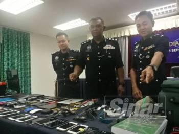 Abdul Aziz (tengah) bersama pegawainya menunjukkan sebahagian barang disyaki hasil jenayah Geng Syed Savanna yang berjaya dirampas susulan tertangkapnya tiga individu di Dengkil, Sepang, sejak 17 Mei lalu.