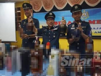 Johari (tengah) menunjukkan sebahagian minuman keras pelbagai jenama dirampas pada sidang media di Dewan Mesra JKDM, Jalan Pegawai, hari ini.