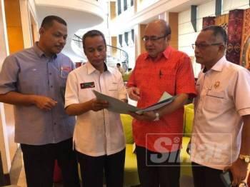Abdul Aziz Derashid (dua, kanan) Aimi (tengah) meneliti permohonan saman yang difailkan mereka sambil diperhatikan Nadzri (kiri) dan Awang kanan.