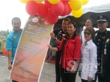 Azman (kiri) memegang banting Majlis Pelancaran Ops Bersepadu dan Kempen Keselamatan Jalan Raya bersempena Perayaan Hari Raya Aidilfitri Peringkat Kedah 2019 di Plaza Tol Hutan Kampung, semalam.