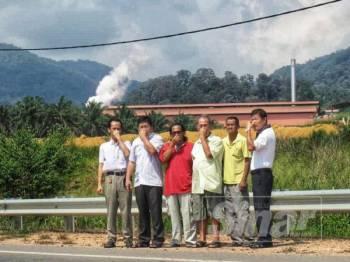 Chen Choo (dua, kiri) ketika mengadakan lawatan kerja, kelmarin bersama sebahagian penduduk yang menunjukkan kilang sawit di belakang mereka yang menghadapi pencemaran bau.