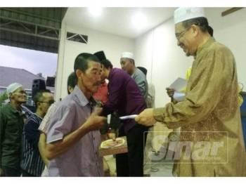 Ir Phahrolrazi (kanan) menyerahlan sumbangan wang tunai kepada salah seorang asnaf pada Majlis Iftar Pertubuhan Peladang, Majlis Pengurusan Komuniti Kampung (MPKK) dan Kawasan Rukun Tetangga (KRT) Dewan Undangan Negeri ( DUN) Alor Mengkudu di Dewan D'Awangan, di sini, semalam.