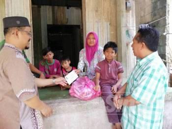 Mohd Rusli (kiri) bersama Dr Zulkepli menyampaikan sumbangan wang tunai dan barang keperluan dapur ketika menziarahi Samsiah Alni di rumahnya di Kampung Cherang Melintang, Tumpat.