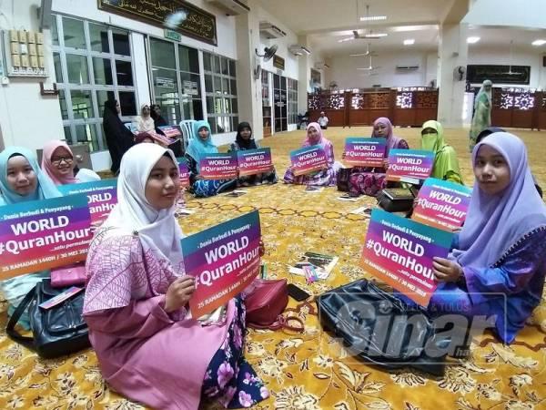 Peserta memegang poster World #QuranHour sebelum majlis membaca al-Quran bermula.